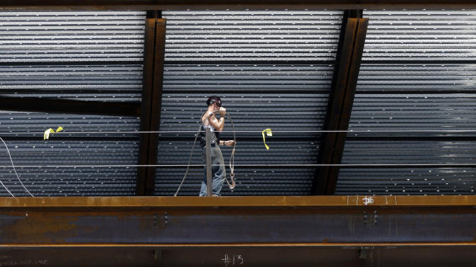 In this July 9, 2012 photo, a construction worker carries equipment on the job in Boston. U.S. service companies, which employ 90 percent of Americans, grew at a slightly faster pace in July. The Institute for Supply Management reported Friday, Aug. 3, 2012, that its index of non-manufacturing activity picked up slightly last month with a reading of 52.6. That was a tiny improvement from June's reading of 52.1, which had been the lowest since January 2010. Still, any reading above 50 indicates expansion. (AP Photo/Elise Amendola)