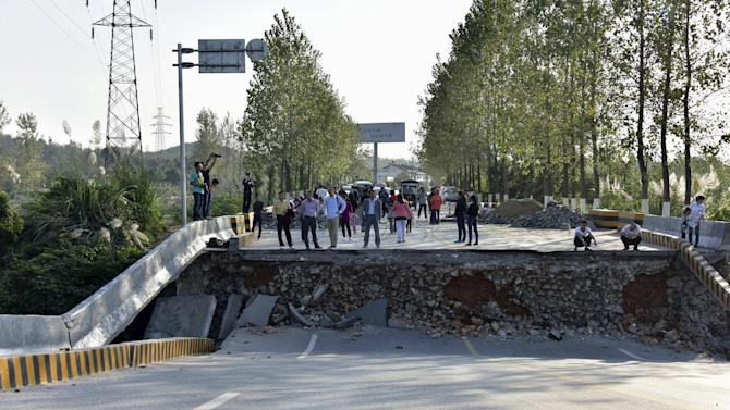 People look on near a section of a bridge which has collapsed, in Chibi, Hubei province,
