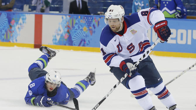 USA forward Phil Kessel take the puck away from Slovenia forward Ziga Jeglic during the 2014 Winter Olympics men's ice hockey game at Shayba Arena Sunday, Feb. 16, 2014, in Sochi, Russia. (AP Photo/Matt Slocum)
