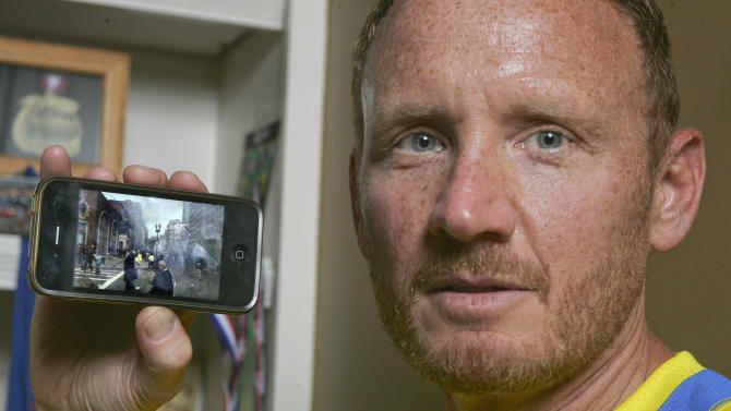 David Green holds up his iPhone with a photo on it he took after the Boston Marathon bombing Friday, April 19, 2013, at his home in Jacksonville, Fla. Seconds after the Boston Marathon bombs exploded, Green pulled out his smartphone and took the photo of the chaos developing a couple hundred yards in front of him -- the smoke, the people running in panic. The Jacksonville businessman then put his phone back in this pocket and went to help the injured. It wasn't until Thursday that Green realized what he had – a picture of suspect Dzhokhar A. Tsarnaev, distinctive in his backward white baseball cap, walking away from the scene. (AP Photo/Phil Sears)