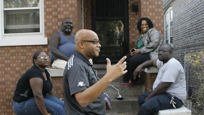 """In this Oct. 24, 2012 photo, Unity Party candidate Lance Tyson, center, campaigns in Illinois' 10th legislative district in Chicago where he is challenging Derrick Smith. Smith, a former state representative indicted on federal bribery charges - and on the ballot as a Democrat - is fighting to regain the seat he was expelled from in August. A victory for Smith could be another embarrassment for a party and a state that already have a reputation for corruption, party leaders say, and they are going to great lengths to defeat Smith. The district's Democratic party committeemen announced a new political party called the """"10th District Unity Party"""" and selected Tyson as their candidate to take on Smith. (AP Photo/Charles Rex Arbogast)"""
