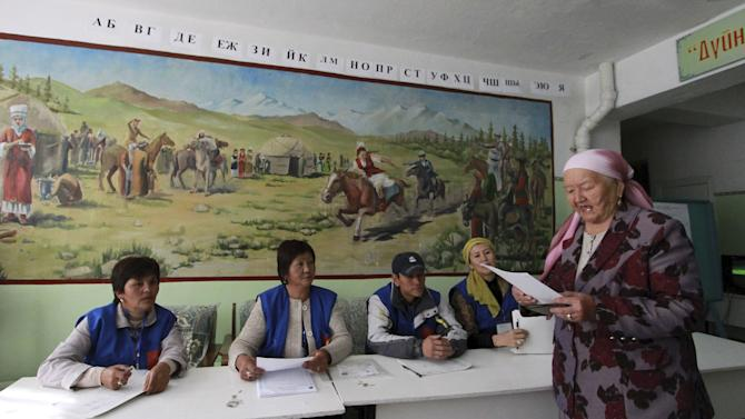 An elderly woman carries her ballot during a parliamentary election at a polling station in the village of Gornaya Maevka, southeast of Bishkek