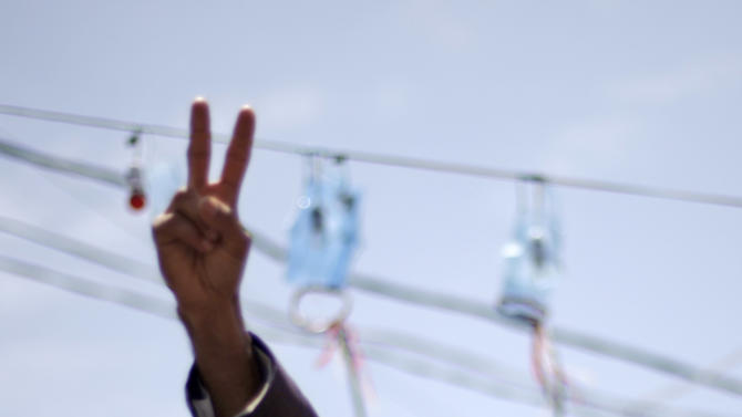 A protestor flashes the victory sign and  shouts slogans during a demonstration demanding the resignation of Yemen's President Ali Abdullah Saleh in Sanaa, Yemen, Monday, Sept. 5, 2011. (AP Photo/Hani Mohammed)
