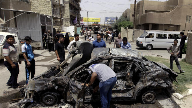 Civilians inspect the site of a parked car bomb attack near a popular restaurant in the Ur neighborhood in northern Baghdad, Iraq, Thursday, May 30, 2013. A series of morning bomb explosions in Baghdad and the northern Iraqi city of Mosul on Thursday, killed and wounded dozens of people, police said, in the latest eruption of violence rattling the country. (AP Photo/Khalid Mohammed)