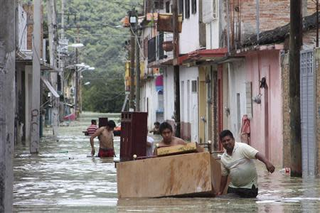 People move furniture through a flooded street in Tixtla