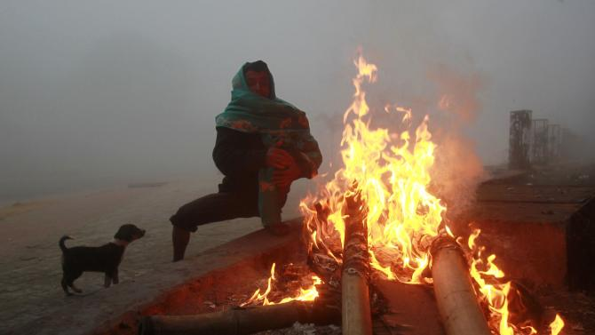 A man warms himself by  bonfire as puppy looks on cold and foggy morning in Agartala