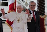 Pope Benedict XVI waves to the crowd as he stands next to Lebanese President Michel Sleiman (R) during a welcoming ceremony at Beirut's Rafiq Hariri International Airport