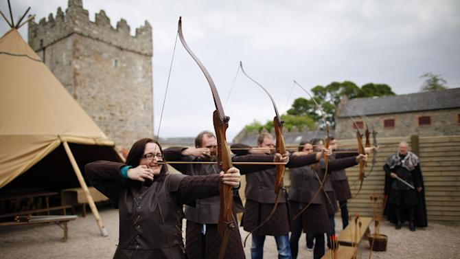 In this photo taken June 13, 2014, Game of Thrones tourists take part at clearsky adventure which has built an exact replica of Winterfell Archery range in the same spot where filming took place at castleward, Strangford, Northern Ireland. (AP Photo/Peter Morrison)