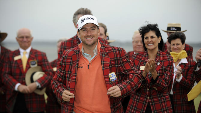 Graeme McDowell, of Northern Ireland, puts on his new plaid jacket after winning the RBC Heritage golf tournament in Hilton Head Island, S.C., Sunday, April 21, 2013. McDowell defeated Webb Simpson in a playoff. (AP Photo/Stephen Morton)