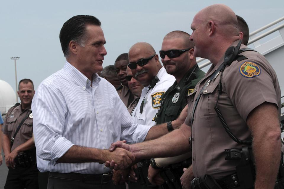 Republican presidential candidate, former Massachusetts Gov. Mitt Romney greets highway patrol officers before boarding the campaign charter flight, Monday, Aug. 13, 2012, in St. Augustine, Fla.  (AP Photo/Mary Altaffer)