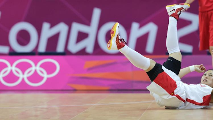 China guard Song Xiaoyun hits the floor after a collision during a basketball game against the Czech Republic at the 2012 Summer Olympics, Saturday, July 28, 2012, in London. (AP Photo/Charles Krupa)