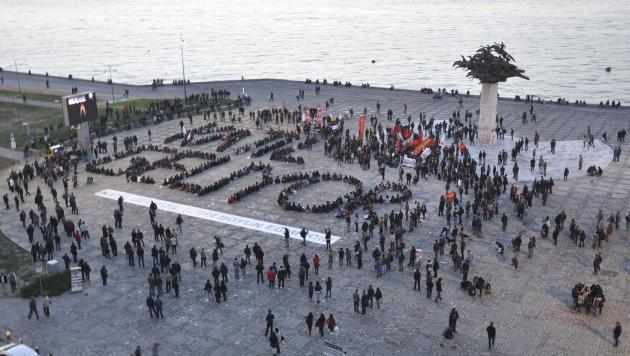 "Demonstrators form a slogan reads that: ""Murderer is coming"" during an anti-government protest at Gundogdu square in the Aegean port city of Izmir"