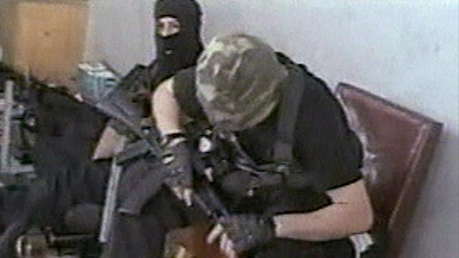 FILE - Hostages sit with their weapons in the school in Beslan, Russia taken  in this undated image from television during the early part of the siege which began on  Sept. 1, 2004 and ended with over 300 people dead. Two suspects in the Boston Marathon bombing have been identified to The Associated Press as coming from a Russian region near Chechnya  In the past, insurgents from Chechnya and neighboring restive provinces in the Caucasus have been involved in terror attacks in Moscow and other places in Russia. (AP Photo/NTV-Russian Television Channel, File)