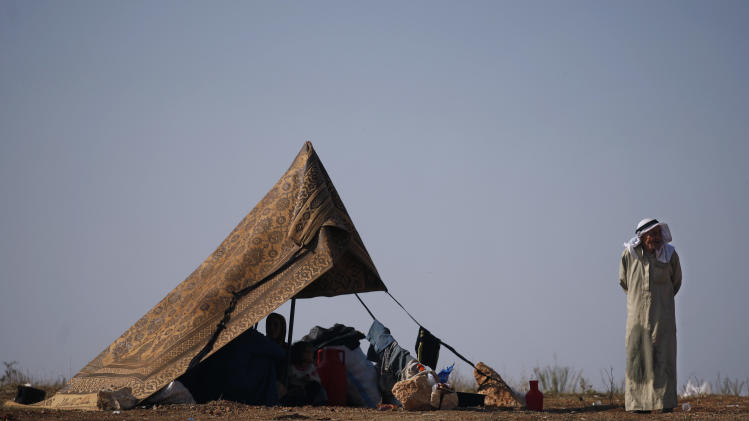 A Syrian family who fled from the violence in their village, sit in a tent at a displaced camp, in the Syrian village of Atma, near the Turkish border with Syria, Monday, Nov. 5, 2012. (AP Photo/ Khalil Hamra)