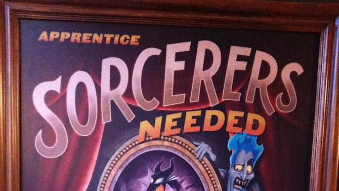 """In this Feb. 15, 2013 photo, a sign encouraging Walt Disney World guests to participate in the """"Sorcerers of the Magic Kingdom"""" game is displayed at the Magic Kingdom theme park in Lake Buena Vista, Fla. The """"Sorcerers"""" game and others like it represent a recent push by Disney World to provide its guests with attractions that allow them to interact with their favorite characters. (AP Photo/Mike Householder)"""