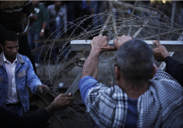 Egyptian protesters take down barbed wire during a demonstration in front of the presidential palace in Cairo, Egypt, Friday, Dec. 7, 2012. Egypt's political crisis spiraled deeper into bitterness and
