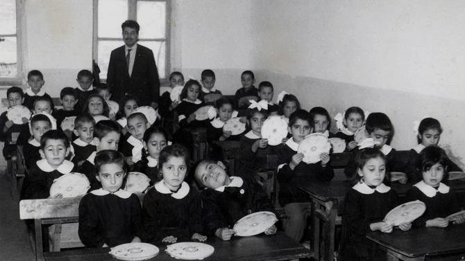 FILE - Undated file photo shows teacher Rasim Kaygusuz, author of Cin Ali, a village character who was created around 1970 for children by Kaygusuz, with his primary school students. If you fail or foul up something in Turkey, one way to laugh it off is to invoke Cin Ali, the squiggly stick figure in a cap whose benign adventures in big-print, picture books helped a generation of Turks learn to read in primary school.(AP Photo/Kaygusuz Family, File)