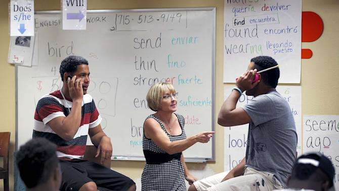 In this May 22, 2014 photo, ESL instructor Carol Gabb, center, helps San Francisco Giants baseball prospects Jose Murel, left, and Reimy Rodriguez converse, in English, on a pretend phone conversation in Scottsdale, Ariz. San Francisco is just one of many clubs putting a stronger emphasis on teaching English basics, including training as to writing checks, using a bank account or mailing a letter. (AP Photo/Matt York)