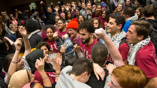 In this photo provided by the The Daily Northwestern, Northwestern University students celebrate after the Associated Student Government Senate passed a Northwestern Divest-sponsored resolution in Evanston, Ill. just before 1:30 a.m. on Thursday, Feb. 19, 2015. The resolution asks the university to divest from six corporations the resolution's sponsors say violate Palestinians' human rights. (AP Photo/The Daily Northwestern, Nathan Richards)