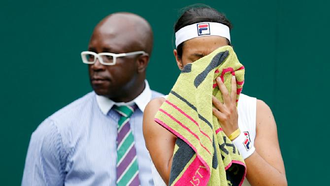 Silvia Soler-Espinosa of Spain wipes her face during her match against Timea Bacsinszky of Switzerland at the Wimbledon Tennis Championships in London