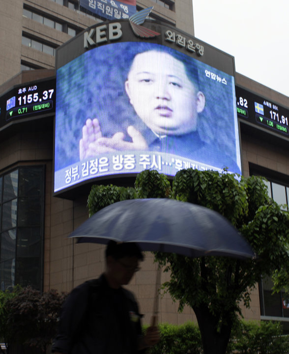 A man walks by a huge screen showing a file footage of Kim Jong Un, the youngest son of North Korean leader Kim Jong Il, in downtown Seoul, South Korea, Friday, May 20, 2011. The young son and heir ap
