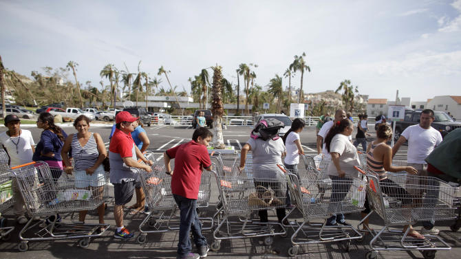 People stand in line to get free food from a Mega Supermarket in Los Cabos, Mexico, Tuesday, Sept. 16, 2014. According to employees the supermarket donated all the food in the store and established a system by which every person had 5 minutes to get whatever they could for free. Desperate locals and tourists were in survival mode in the resort area of Los Cabos also on Wednesday, with electrical and water service still out three days after Hurricane Odile made landfall as a monster Category 3 storm. (AP Photo/Victor R. Caivano)
