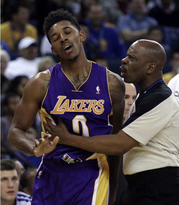 Los Angeles Lakers' Nick Young, left is restrained by referee Derek Richardson during the second half of an NBA basketball game against the Golden State Warriors Saturday, Dec. 21, 2013, in Oaklan