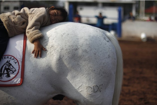 Handicapped girl attends a session of equine-assisted therapy at the Mounted Police Unit in Mexico City