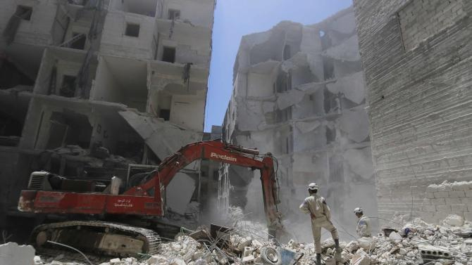A man operates an excavator at a site hit by what activists said was a barrel bomb dropped by forces loyal to Syria's President Bashar al-Assad, in the Al-Fardous neighbourhood of Aleppo