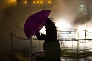 A pedestrian walks into the wind near a steam vent in the financial district, Wednesday, Nov. 7, 2012, in New York. Residents of New York and New Jersey who were flooded out by Superstorm Sandy are waiting with dread Wednesday for the second time in two weeks as another, weaker storm heads toward them and threatens to inundate their homes again or simply leave them shivering in the dark for even longer. (AP Photo/John Minchillo)