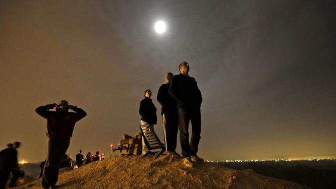 The moon illuminates Israelis standing on a hill at the Israeli town of Sderot, overlooking the Gaza Strip, background right, as they watch a missile, not seen, fired by Palestinian militants from inside Gaza towards southern Israel, Wednesday, Nov. 21, 2012, shortly before a cease-fire is announced between Israel and Hamas. Israel and the Hamas militant group agreed to a cease-fire Wednesday to end eight days of the fiercest fighting in nearly four years, promising to halt attacks on each other and ease an Israeli blockade constricting the Gaza Strip.The deal was brokered by the new Islamist government of Egypt, solidifying its role as a leader in the quickly shifting Middle East after two days of intense shuttle diplomacy that saw U.S. Secretary of State Hillary Rodham Clinton race to the region. (AP Photo/Lefteris Pitarakis)