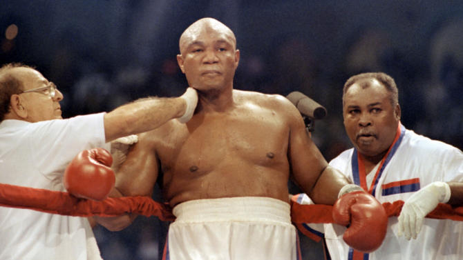 FILE - In this April 20, 1991, file photo, heavyweight challenger George Foreman, center, is tended by veteran trainer Angelo Dundee, left, and former light-heavyweight champion Archie Moore during a title fight against Evander Holyfield in Atlantic City. (AP Photo/Amy Sancetta, File)