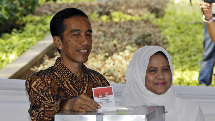 "Indonesian presidential candidate Joko Widodo, popularly known as ""Jokowi"", left, accompanied by his wife Iriana, casts his ballot during the presidential election in Jakarta, Indonesia, Wednesday, July 9, 2014. As the world's third-largest democracy began voting Wednesday to elect a new president, Indonesians are divided between two very different choices: a one-time furniture maker, Jakarta Governor Joko Widodo, and a wealthy ex-army general with close links to former dictator Suharto, Prabowo Subianto. (AP Photo/Dita Alangkara)"