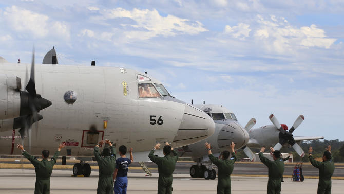 Japan Maritime Self-Defense Force farewell their P-3C Orion as it taxis from the Royal Australian Air Force Pearce Base to commence a search for possible debris from the missing Malaysia Airlines flight MH370, in Perth, Australia, Monday, March 24, 2014. Satellite images released by Australia and China had earlier identified possible debris in an area that may be linked to the disappearance of the flight on March 8 with 239 people aboard. (AP Photo/Paul Kane, Pool)