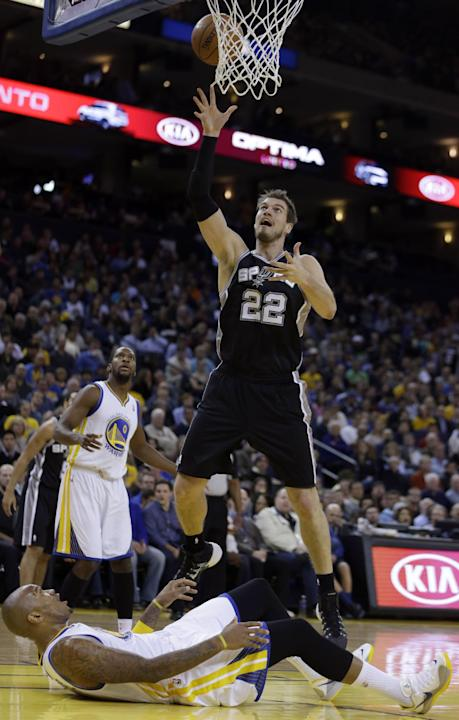 San Antonio Spurs' Tiago Splitter (22) shoots over Golden State Warriors' Marreese Speights during the first half of an NBA basketball game, Thursday, Dec. 19, 2013, in Oakland, Calif