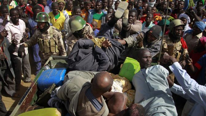 """Malian soldiers throw a  suspected Islamist extremist into the back of an army truck in Gao, northern Mali, Tuesday Jan. 29, 2013. Four suspects were arrested after being found by a youth militia calling themselves the """"Gao Patrolmen"""". Malian soldiers prevented the mob from lynching them. (AP Photo/Jerome Delay)"""
