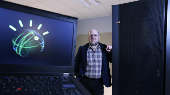 """Jim Hendler, who heads the computer science department at Rensselaer Polytechnic Institute, poses next to the the supercomputer Watson at the Computational Center for Nanotechnology Innovations on Tuesday, Jan. 29, 2013, in Troy, N.Y. Watson, the question-answering supercomputer best known for beating human champions on """"Jeopardy!,"""" is going to college. IBM is announcing Wednesday that it will provide a Watson system to RPI, the first time a version of the computer is being sent to a university. The avatar on the computer screen at left represented Watson on """"Jeopardy!."""" (AP Photo/Mike Groll)"""