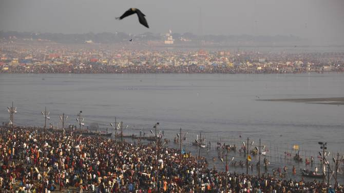 Hindu devotees take a holy dip at 'Sangam', the confluence of Hindu holy rivers Ganges, Yamuna and the mythical Saraswati, during the Maha Kumbh festival at Allahabad, India, Sunday, Feb. 10, 2013.  Led by heads of monasteries arriving on chariots and ash-smeared naked ascetics, millions of devout Hindus plunged into the frigid waters of the holy Ganges River in India on Sunday in a ritual that they believe will wash away their sins. Sunday was the third of six auspicious bathing days during the Kumbh Mela, or Pitcher Festival, which lasts 55 days and is one of the world's largest religious gatherings. (AP Photo /Rajesh Kumar Singh)