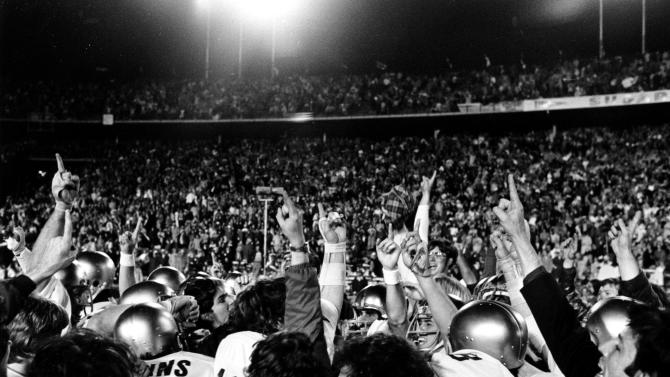 "FILE - In this Dec. 31, 1973, file photo, Notre Dame players team point their fingers skyward as they chant ""we're number one"" after defeating then-undefeated Alabama 24-23 in the Sugar Bowl NCAA college football game in New Orleans. Alabama (11-1) finished the regular season undefeated and was declared the national champion in the coaches poll, where the Irish were ranked No. 4. Notre Dame (11-0) then defeated Alabama in the Sugar Bowl and AP named Notre Dame the national champion. (AP Photo/File)"