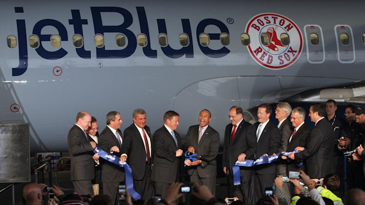 IMAGE DISTRIBUTED FOR JETBLUE AIRWAYS - From left to right are Rich Smythe, Vice President, Corporate Real Estate for jetBlue, Dave Ramage, Vice President of Technical Operations for jetBlue, Jeff Martin, Senior Vice President of Operations for jetBlue, Ed Freni, MassDOT Director of Aviation, Rob Maruster, COO of jetBlue Airways, Massachusetts Governor Deval Patrick, U.S. Congressman Michael Cupiano,  Richard Davey, MassDOT Secretary and CEO, Thomas Glynn, Massport CEO and Executive Director, Massachusetts Senator Tom McGee, and Archie Vega, Manager of Maintenance for jetBlue Airways.  All participated in a ribbon cutting ceremony to celebrate jetBlue Airways move to historic Hangar 8  at Logan International Airport in Boston, Monday, Dec. 10, 2012.  (Aynsley Floyd/AP Images for jetBlue Airways)