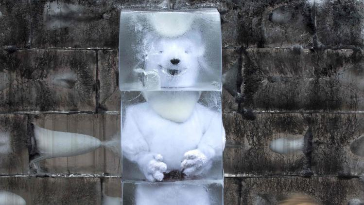 A polar bear replica, which is displayed by Greenpeace activists, is seen inside a block of ice in Sao Paulo