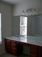 The master bathroom before had beautiful cabinets and sophisticated light fixtures, and it just…