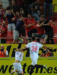 Sevilla&#39;s Piotr Trochowski (L) celebrates with Tomas Alberto Botia after scoring during their Spanish league football match against Real Madrid at the Ramon Sanchez Pizjuan stadium in Sevilla. Sevilla won 1-0
