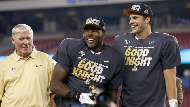 Central Florida head coach George O'Leary, left, watches as players Terrance Plummer, middle, and Blake Bortles, right, smile at the crowd and teammates after a Fiesta Bowl NCAA college football game win against Baylor Wednesday, Jan. 1, 2014, in Glendale, Ariz. Central Florida defeated Baylor 52-42. (AP Photo/Ross D. Franklin)