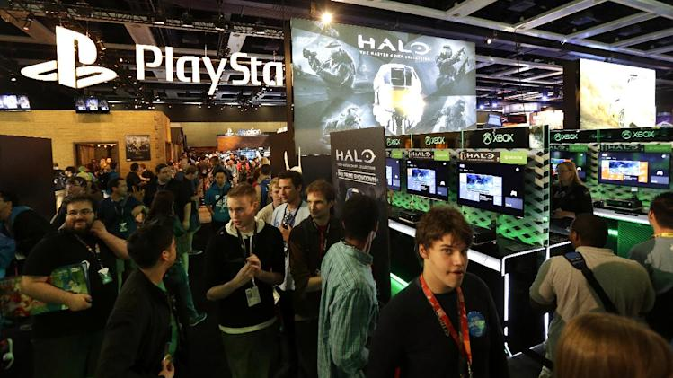 Attendees at the Penny Arcade Expo, a fan-centric celebration of gaming in Seattle, walk past adjoining displays from gaming giants Sony PlayStation and Microsoft's Xbox One, Friday, Aug. 29, 2014. The event is expected to be attended by roughly 85,000 gamers and will include concerts, game tournaments and previews of upcoming titles. (AP Photo/Ted S. Warren)
