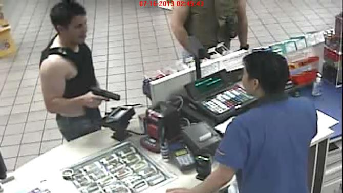 In this image taken from surveillance video provided by the Pima County Sheriff's Department, a man identified as off-duty Tucson, Ariz. police officer Kyle James McCartin, 23, wearing a bullet proof vest, aims a gun at a Giant Gas Station clerk in Tucson early Tuesday, July 16, 201. Authorities say two men wearing bullet-proof vests approached the gas station clerk and one of them later identified as McCartin allegedly pulled out a gun and pointed it twice at the clerk. McCartin was taken into custody early Tuesday, and was later fired. (AP Photo/Pima County Sheriff's Department)