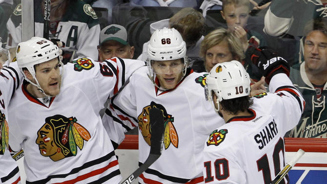 Chicago Blackhawks center Andrew Shaw, left, and left wing Patrick Sharp (10) congratulate right wing Patrick Kane (88) after he scored on Minnesota Wild goalie Devan Dubnyk during the first period of Game 3 in the second round of the NHL Stanley Cup hockey playoffs in St. Paul, Minn., Tuesday, May 5, 2015. (AP Photo/Ann Heisenfelt)