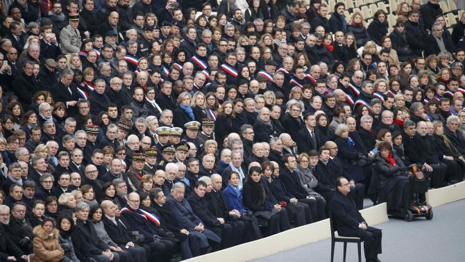 French President Francois Hollande sits in front of members of French government and French officilas during a ceremony to pay a national homage to the victims of the Paris attacks at Les Invalides monument in Paris