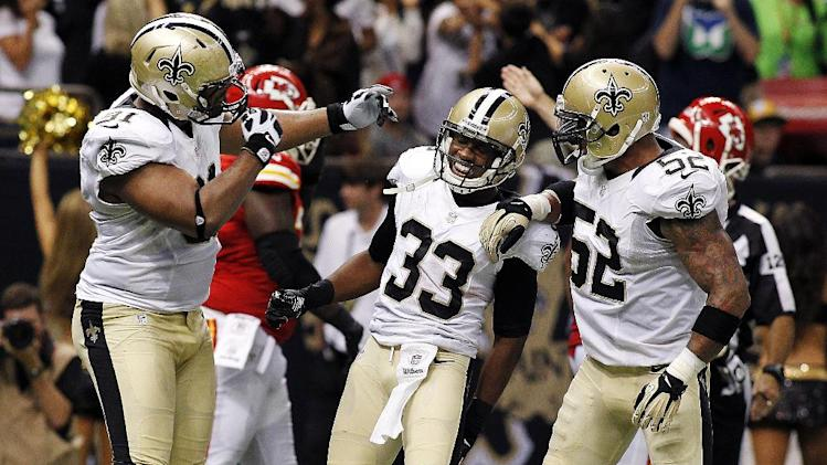 New Orleans Saints cornerback Jabari Greer (33) celebrates his interception with defensive end Will Smith (91) and linebacker Jonathan Casillas (52) in the second half of an NFL football game in New Orleans, Sunday, Sept. 23, 2012. (AP Photo/Jonathan Bachman)
