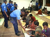Sri Lankan sailors assist rescued survivors at Oluvil fisheries harbour in eastern Sri Lanka earlier this month. A boatload of Myanmar nationals rescued from a sinking wooden craft off Sri Lanka's east coast after two months at sea had been trying to reach Australia, local police said Sunday